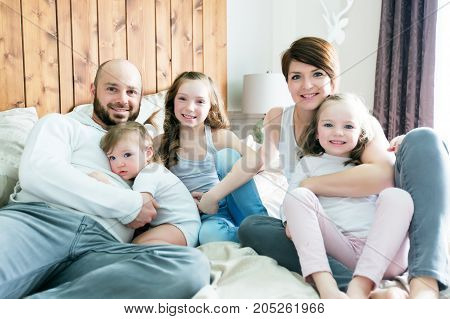 A Young happy family of five on bedroom