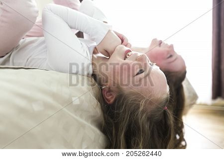 two sister lay on bed at home