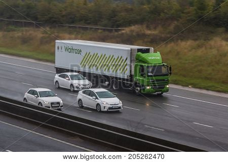 Redbourn UK - September 21 2017: Lorry belonging to the British Waitrose Supermakret in motion on the motorwey M1 in a rainy weather.