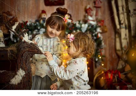 Happy little sisters  playing near a fireplace at Christmas Eve