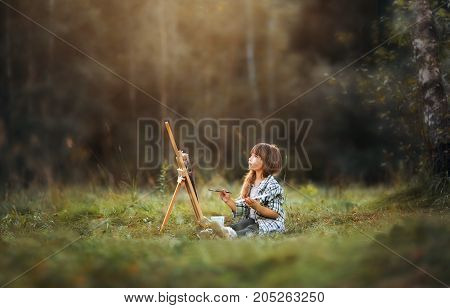 Little girl painting at easel in autumn park
