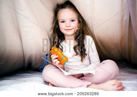 A Little girl reading fairy tales book under the covers at the evening with lantern.