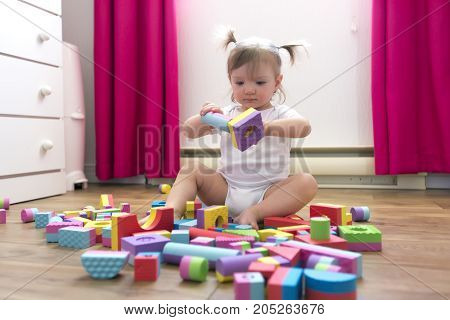 A kid girl playing block toys at home