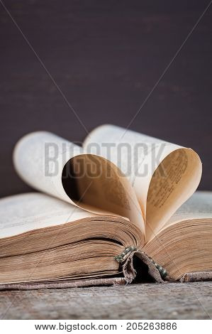 An old book with heart-shaped pages vertical view