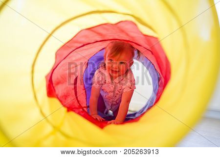 A Happy toddler plays indoor in a tunnel