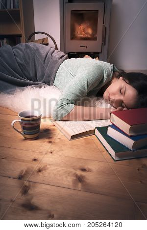 Vertical image with a young beautiful woman sleeping on a white fur direct on the floor in front of a fireplace surrounded by books.