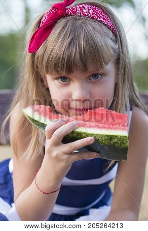 Close up cute little girl with beautiful blue eyes eating watermelon outdoors. Child healthy food.