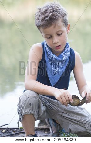 Portrait of a little sweet boy sitting at the river and collecting seashell and enjoy the beautiful and sunny day