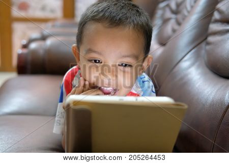 Close up of little boy watching cartoons on the digital tablet at night.