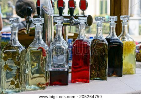 closed glass bottles with colored drinks on the table