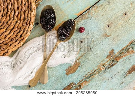 Black berries in spoons and wooden background.