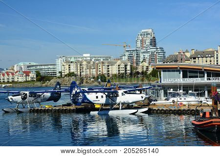 Victoria BC,Canada,September 22nd 2017.Seaplane  terminal along with float planes and high end real estate condos in Victoria 's inner harbor.Come to Victoria and play.