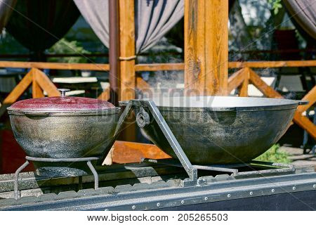 A closed pan and a bowl of food stand on a stove in the street