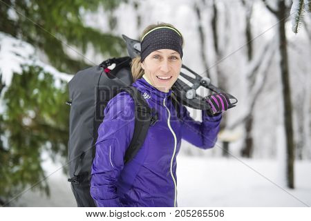 A Winter snowshoeing. Young outdoorswoman hiker holding snowshoes outside in the snow