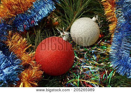 Two colored New Year's balls among bright ornaments and needles