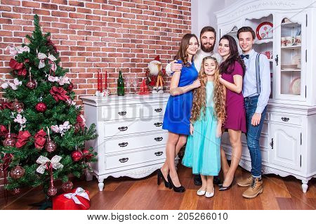 Beautiful Young Family Enjoying Christmas Time And Hugging With Love.