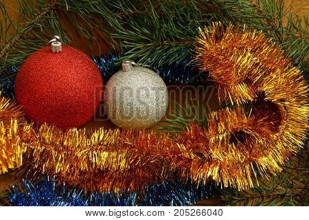 Two New Year's balls among bright ornaments and needles