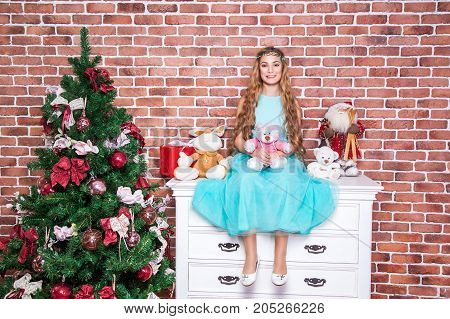 Cheerful Teenage Long Haired Blonde Sit On A White Nightstand Near Christmas Tree.