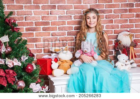 Gifts And Christmas Concept. Teenage Long Haired Blonde Sit On A White Nightstand Near Christmas Tre