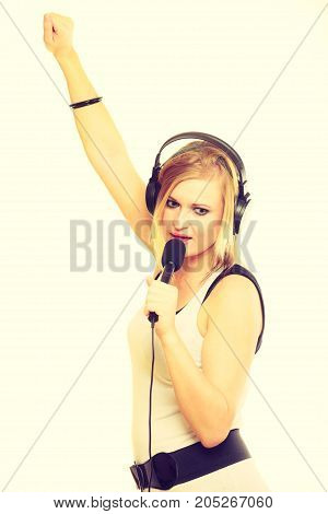 Talent and show. Young blonde talented girl showing her passion by singing to microphone. Female singer sing song.