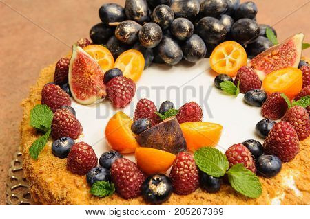 honey cake decorated with fruits and berries, decorate with gold kandurin, grapes, figs, kumquat, decorate with golden candurin, menu idea