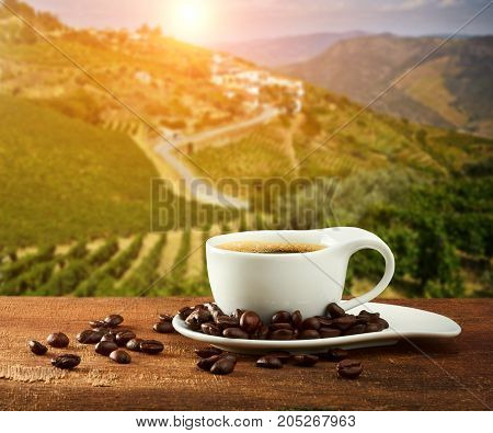 Coffee cup with Coffee beans on the wooden table and plantations background