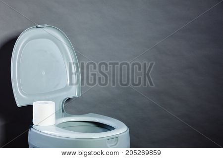 Open portable toilet bowl with paper roll copy space for text