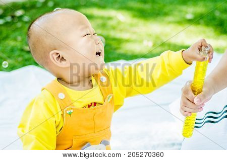 a baby sits on the mat in the park laughing