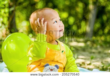 a baby sits on the mat in the park touching his head