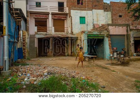 Agra, India - September 20, 2017: Two beautiful litle girls saying hello to the camera of a foreign tourist, surrounding of old building houses, over a stoned ground, in the street in Agra city in India.