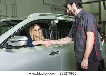 An auto mechanic and female customer in garage