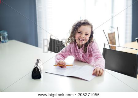 A cute girl writing with pen at the table