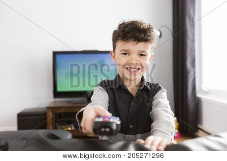 A little boy watching TV lying in the living-room