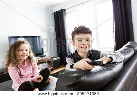 Two young children in living room with flat screen television