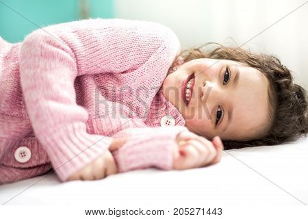 A Happy child in the bed wearing in pink
