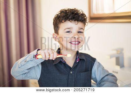 A kid boy brushing teeth on the bathroom