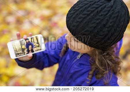 An Adorable little girl in a autumn forest