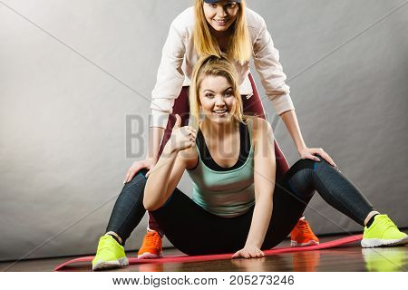 Young blonde woman in sportswear sitting on wooden floor indoor stretching legs with her female trainer. Training at home being fit and healthy.