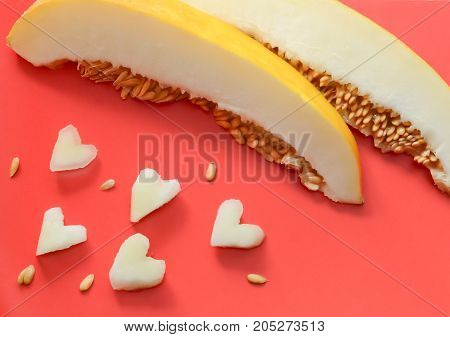 slices of melon on a red background pieces in the shape of a heart and seed
