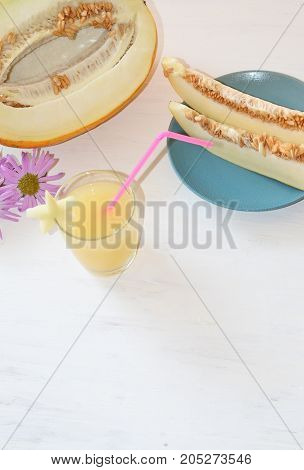 cut the melon next to a glass of smoothie with a slice of melon the star of straw next to an Aster flower all on wooden white background