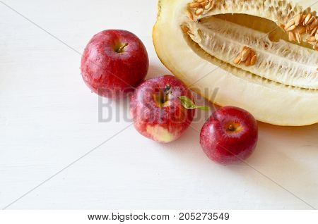 three red apples and pieces of melon on the plate and cut the melon next on white background