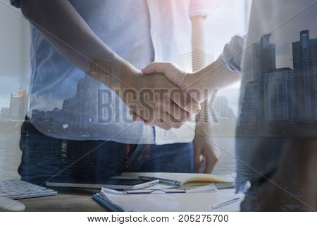double exposure businessman shaking hand and city concept as team work and cooperation in success business