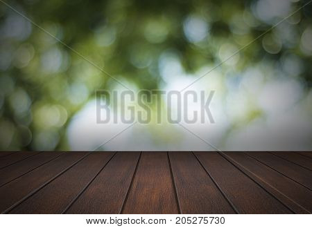 Empty wooden table floor or shelf on soft bokeh and blur green nature background copy space for putting object to display and advertise