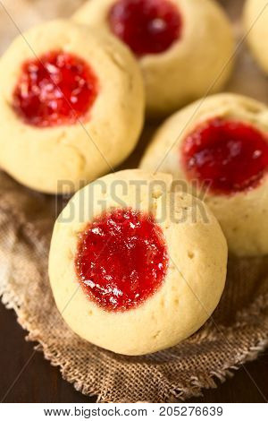 Thumbprint Christmas cookies filled with strawberry jam photographed with natural light (Selective Focus Focus diagonally through the middle of the first cookie)