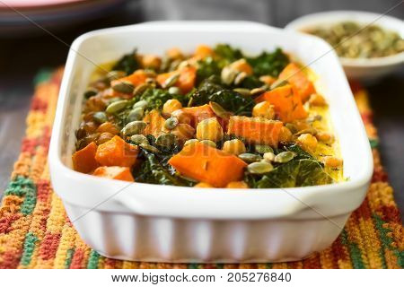 Baked pumpkin kale and chickpea casserole with pumpkin seeds on top in casserole dish photographed with natural light (Selective Focus Focus one third into the dish)