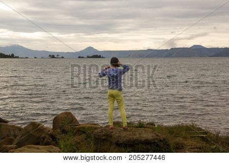 woman standing on rock looking at the lake toba
