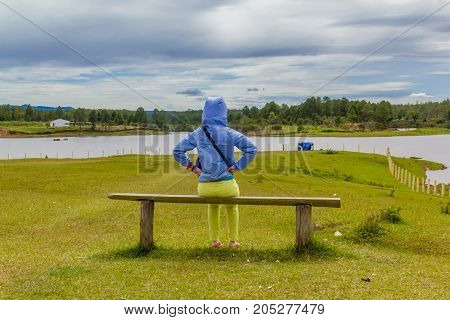 woman  siting on chair looking at the lake
