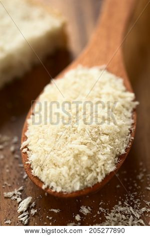 Panko Japanese flaky bread crumbs on wooden spoon photographed with natural light (Selective Focus Focus one third into the breadcrumbs on the spoon)