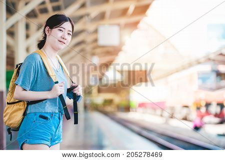 Teen Asian girl waiting for checked baggage train platform area prepared to ready to go sightseeing by the provinces in the country Thailand on weekends. From Bangkok to Chiang Mai