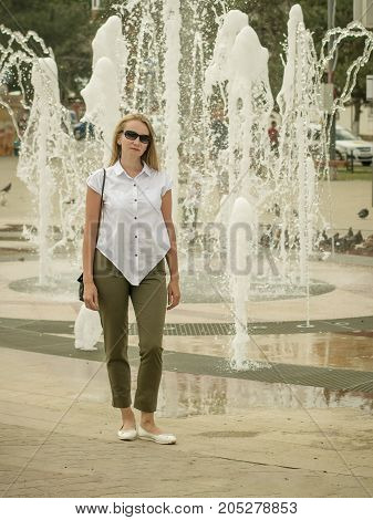 Beautiful woman with bag on your shoulder glasses. Portrait of a beautiful woman on the background of the fountain.